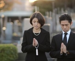 墓前で手を合わせる男女