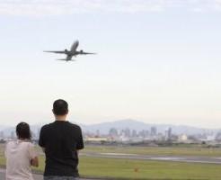 飛行機を見上げる母親と父親