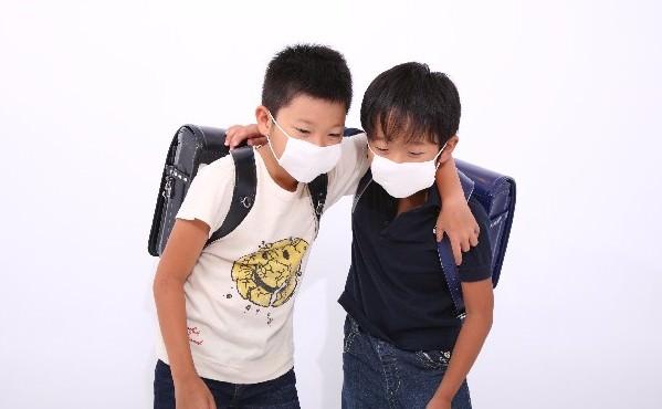 風邪気味で肩をくむ小学生