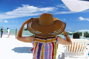 沖縄の海に座る麦わら帽の女性