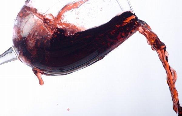グラスからこぼれる赤ワイン