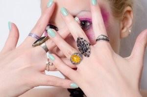 指輪をはめた両手で顔を隠す女性